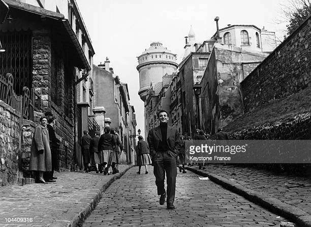The singer Charles AZNAVOUR walking down a street of Montmartre Paris