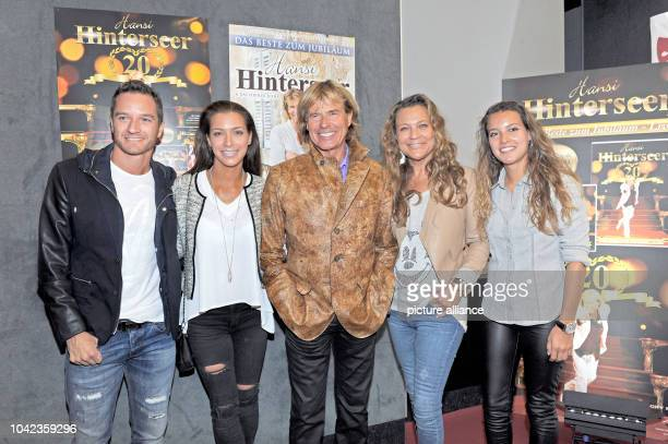 The singer Hansi Hinterseer, his wife Romana , his daughters Laura and Jessica with her boyfriend Timo Scheider smile at the Filmtheater in...
