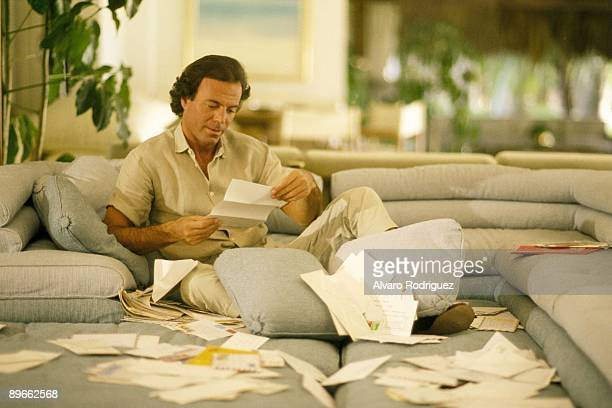 The singer Julio Iglesias at his home in Miami Sat down in an armchair reading letters