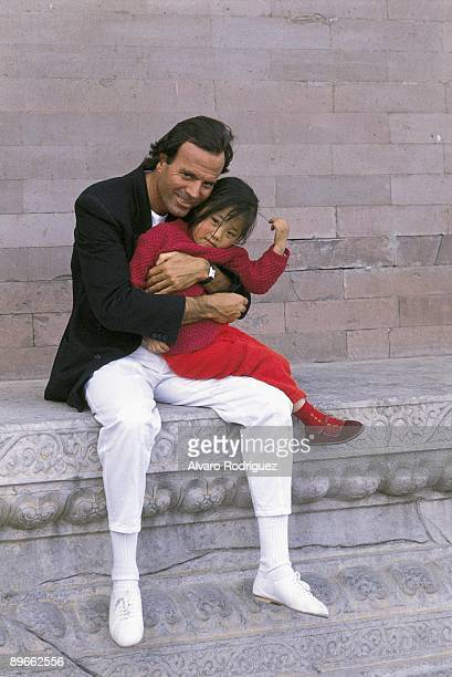 The singer Julio Iglesias in the Forbidden City With a Chinese girl in his arms