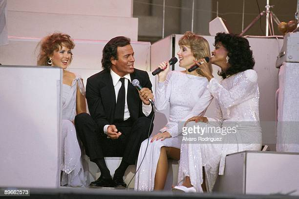 The singer Julio Iglesias with the choir singers In a concert