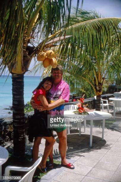 The singer Klaus Baumgart poses on vacation probably on the Bahamas in the outside area of the hotel with his wife Ilona SchulzBaumgart under palm...