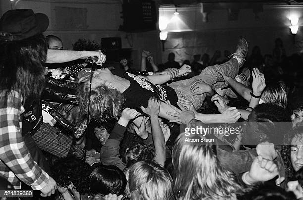 The singer of a band holds the microphone out for a crowd surfer to sing during a rowdy punkmetal concert