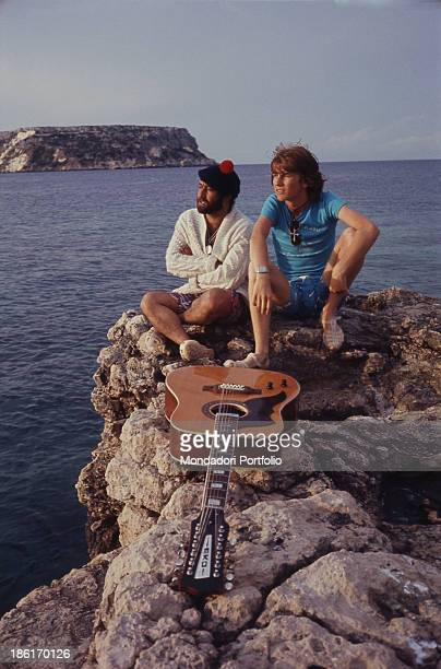 The singers Lucio Dalla and Rosalino Cellamare seated on a rock with a guitar behind them the sea Tremiti Islands Italy August 1971