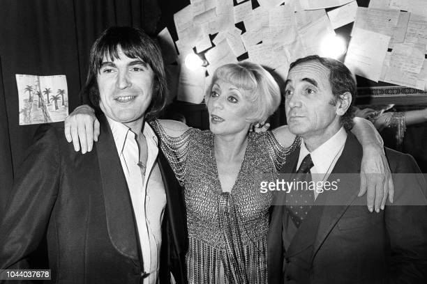 The singers Serge Lama and Charles Aznavour greet the singer and whimsical Annie Cordy after performing on stage at the Olympia in Paris on December...