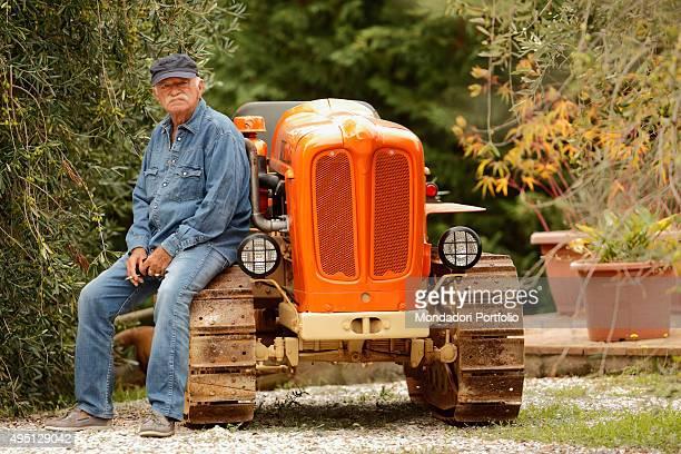 The singersongwriter and musician Gino Paoli smoking a cigarette on a tracked tractor in a photocall shooted in his land in Maremma Campiglia...