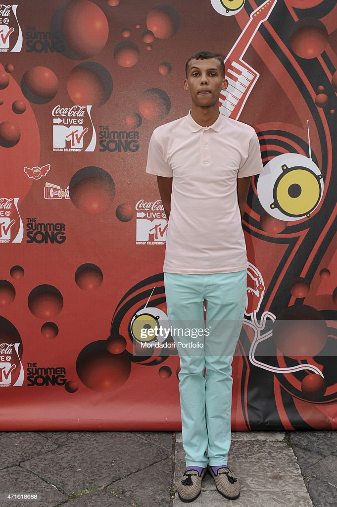 the singer songwriter stromae posing in front of the poster news