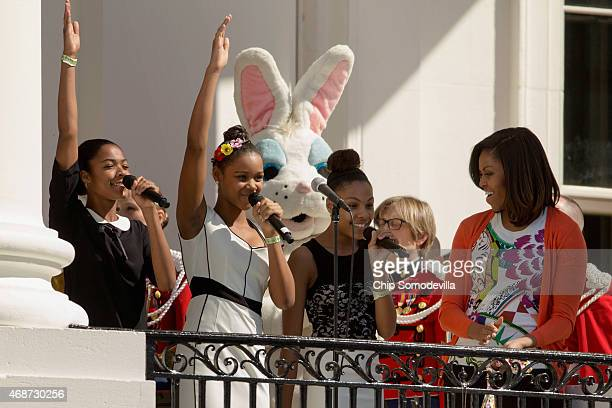 The singing group iD4Girls perform the national anthem as first lady Michelle Obama looks on during the White House Easter Egg Roll on the South Lawn...