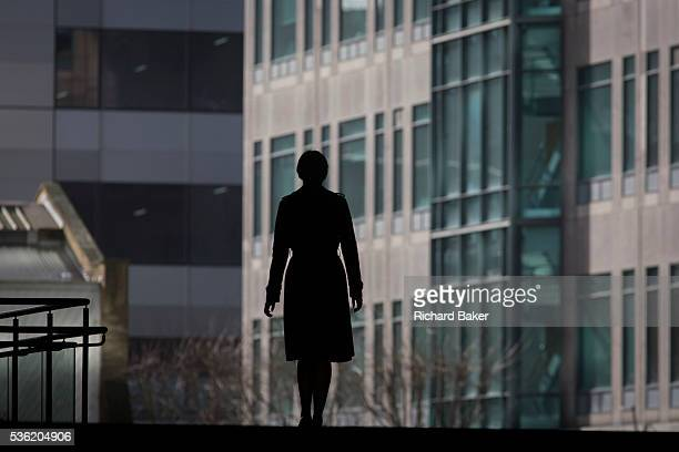 The single silhouette of woman walking through the Broadgate corporate offices development in the City of London With both hands at her side the lone...