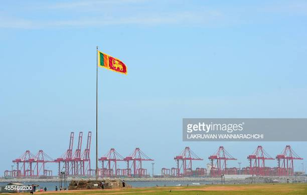 The Sir Lankan national flag is pictured as gantry cranes are see at the new Chinesemajority owned Colombo International Container Terminal in...