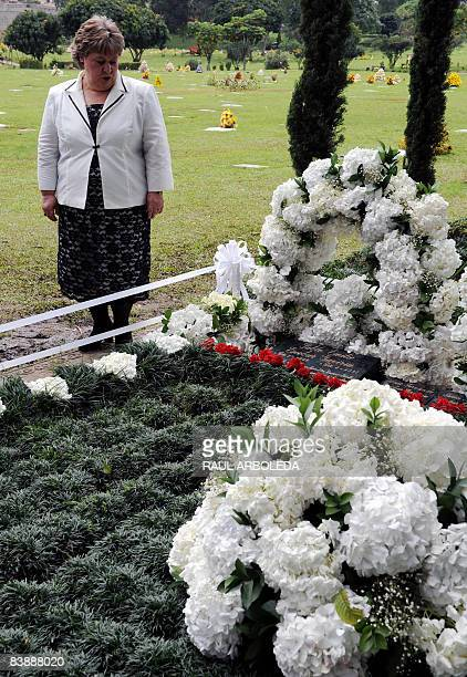 The sister of Colombian drug lord Pablo Escobar Luz Maria Escobar prays next to his tombstone on December 2 in Medellin Antioquia department Colombia...