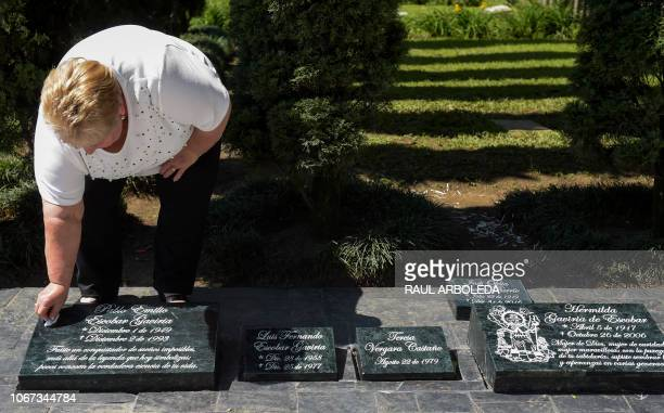 The sister of the Colombian drug lord Pablo Escobar Luz Maria Escobar cleans a plaque on his tomb at the Montesacro cemetery in Medellin Colombia on...