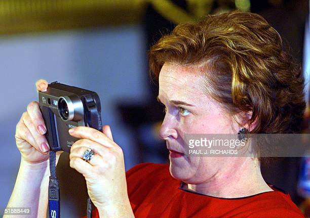 The sister of US President George W Bush Dorothy 'Doro' Bush takes a photograph of her brother during a ceremony 01 February in the East Room of the...