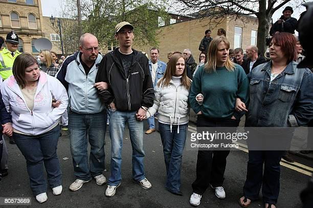 The six close friends and neighbours of Karen Matthews link arms as Matthews leaves Dewsbury Magistrates court today Amanda Hyett Neil Hyett Pete...