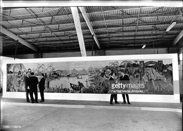 The size of the mural with the artist at right wearing glasses speaking with Mr Kale in front of the workA woodinlay mural measuring 37 feet by 7...