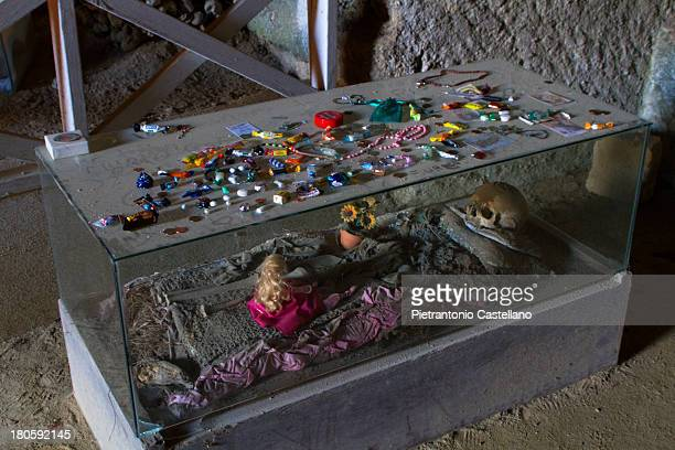 The skeleton of a teenager is covered with votive gifts in the Fontanelle Ossuary in Naples, Italy. Most of the gifts are objects thought to please a...