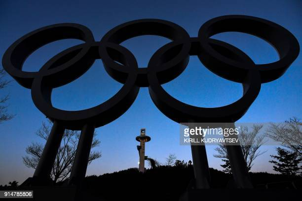TOPSHOT The ski jump tower is seen behind the the Olympic rings ahead of the Pyeongchang 2018 Winter Olympic Games in Pyeongchang on February 6 2018...