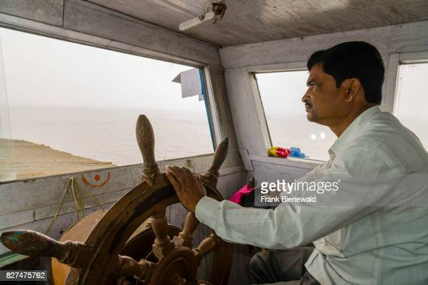 The skipper of a ferry boat full with pilgrims is driving for Ganga Sagar Island in the Gulf of Bengal