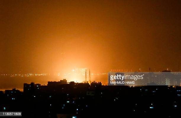 TOPSHOT The sky above buildings on the Gaza Strip glows orange during an Israeli air strike in Gaza city late on March 14 2019 The Israeli military...