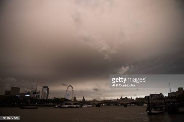 The sky darkens over the river Thames in London on October 16 2017 caused by warm air and dust swept up by storm Ophelia The sun shone red and the...