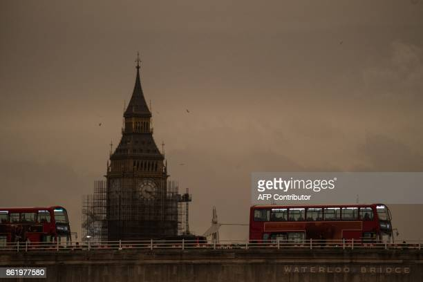 The sky darkens over the Waterloo Bridge and Elizabeth Tower in London on October 16 2017 caused by warm air and dust swept up by storm Ophelia The...