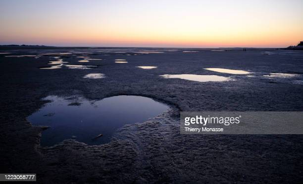 The sky is seen on a salt Puddle on the beach at low tide on June 24, 2020 in Le Crotoy, France. Le Crotoy is located on the north shore, at the...