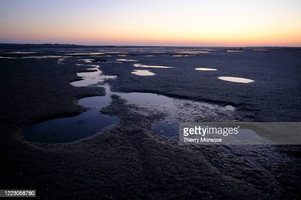 The sky is seen on a salt Puddle on the beach at low tide on June 24 2020 in Le Crotoy France Le Crotoy is located on the north shore at the bottom...