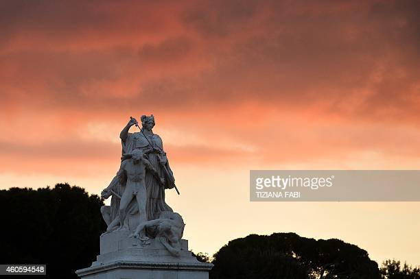 The sky turns orange at sunset in Piazza Venezia on December 17 2014 AFP PHOTO / TIZIANA FABI
