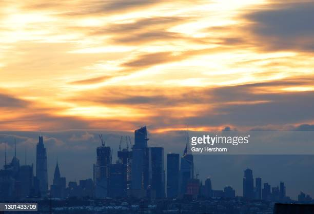 The sky turns orange over the skyline of midtown Manhattan, Hudson Yards and the Empire State Building as the sun rises in New York City on February...