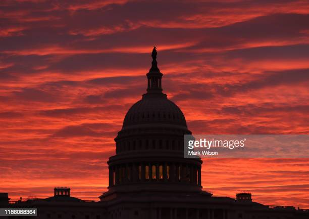 The sky turns to a fiery color as the sun begins to rise behind the US Capitol building on November 7 2019 in Washington DC Chairman of the House...