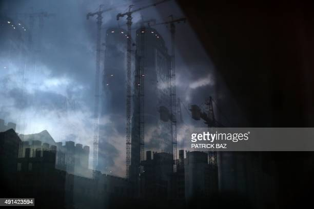 The skyline of Beirut's Ashrafiyeh neighborhood reflects in the window of an apartment on October 5 2015 Lebanon is buzzing with buildings and the...