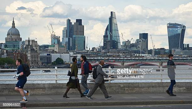 The skyline of buildings in The City of London is seen from Waterloo Bridge as pedestrians walk by in central London on May 23 2016 With one month to...