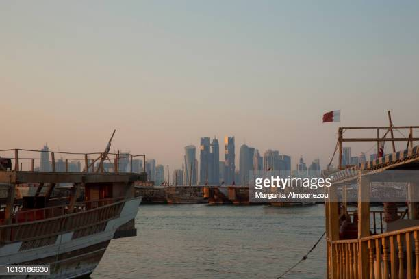 The skyline of Doha city framed by wooden boats