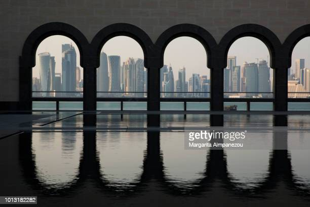 The skyline of Doha city under arches reflected in water