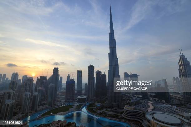 The skyline of Dubai and the high Burj Khalifa are pictured at sunset on February 9, 2021.