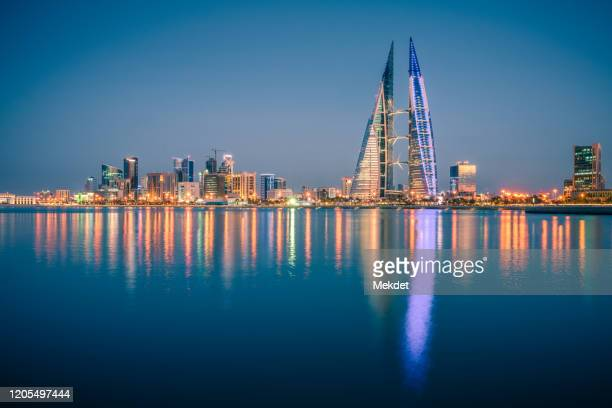 the skyline of illuminated manama city waterfront at night, manama city, bahrain - bahrain stock pictures, royalty-free photos & images