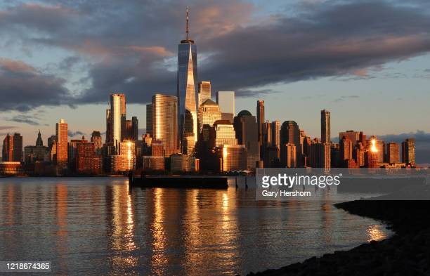 The skyline of lower Manhattan and One World Trade Center shines in gold as the sun sets in New York City on April 13 2020 as seen from Jersey City...