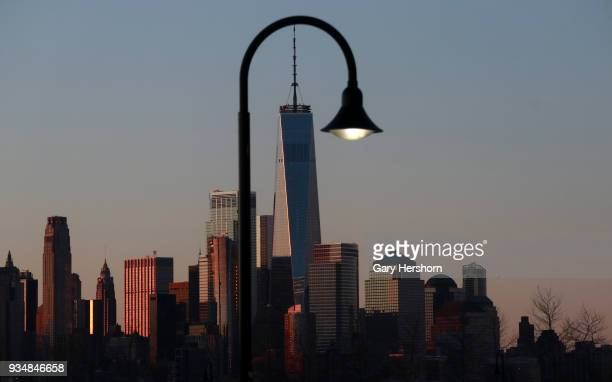 The skyline of lower Manhattan and One World Trade Centers are lit at sunrise in New York City on March 18 2018 as seen from Hoboken New Jersey