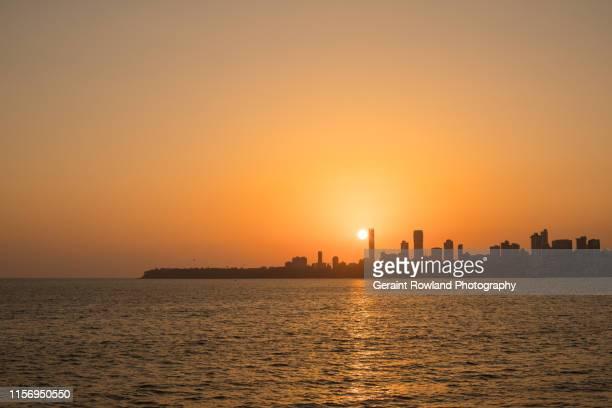 the skyline of mumbai at sunset - mumbai stock pictures, royalty-free photos & images