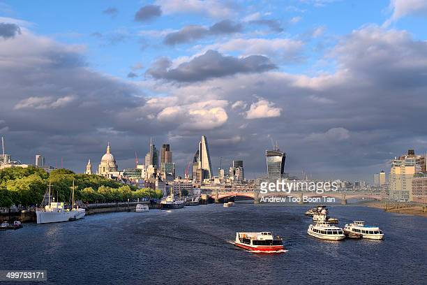CONTENT] The skyline of the City of London is lit by the evening sun as boats sail down the Thames As seen from Waterloo Bridge