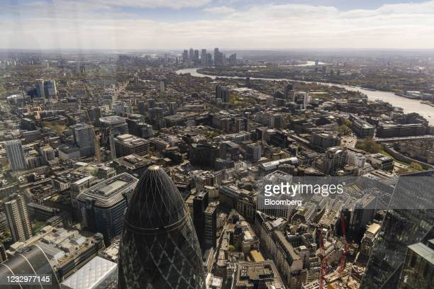 The skyscraper at 30 St Mary Axe, also known as The Gherkin, in the City of London, bottom left, and the Canary Wharf, business, financial and...