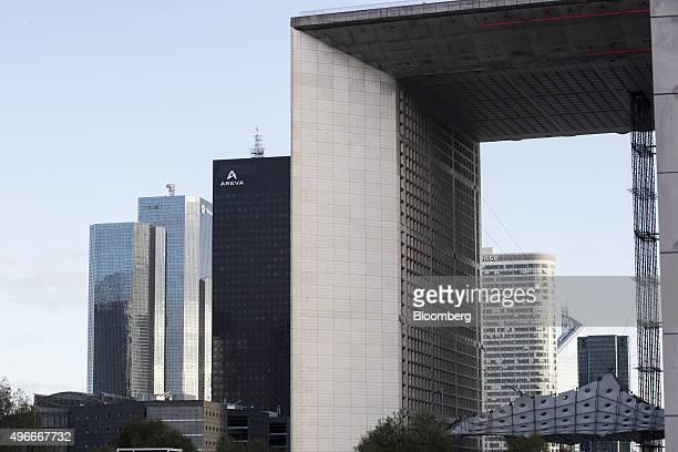 The skyscraper headquarter offices of Total SA left and Areva SA center stand beyond the Grande Arche de la Defense monument in La Defense business...