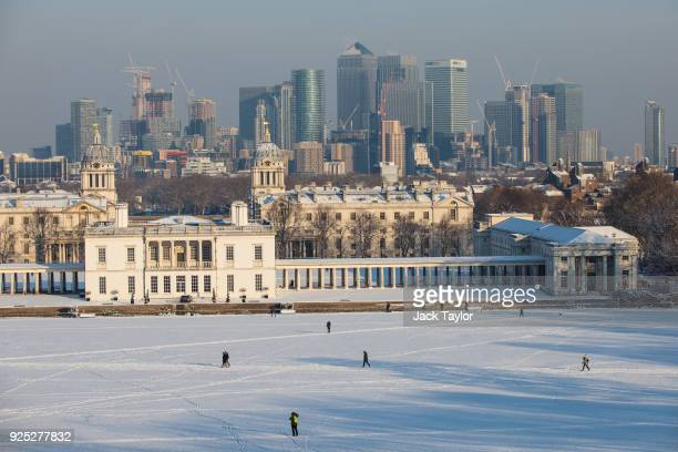 The skyscrapers of Canary Wharf are seen as the sun rises on a snow covered Greenwich Park on February 28, 2018 in London, United Kingdom. Freezing...