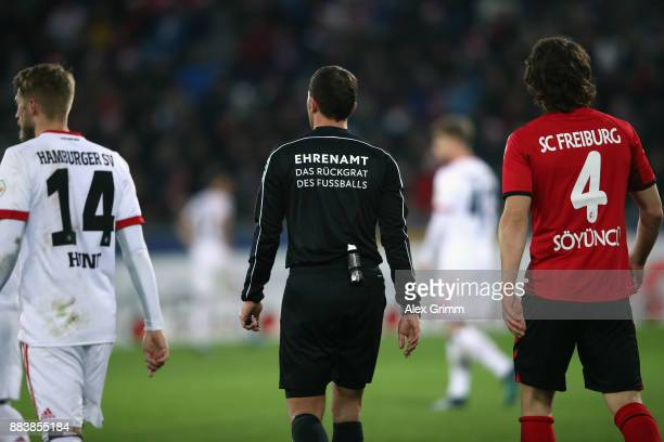 The slogan 'Ehrenamt das Rueckgrat des Fussballs' is seen on the jersey of referee Benjamin Brand during the Bundesliga match between SportClub...