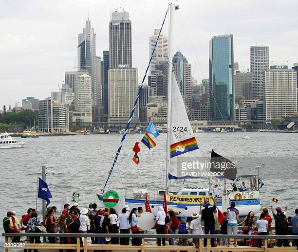 The sloop Eureka that will sail to Nauru Island as part of a Flotilla of Hope passes by a group of protestors in Sydney 11 April 2004 A broad...