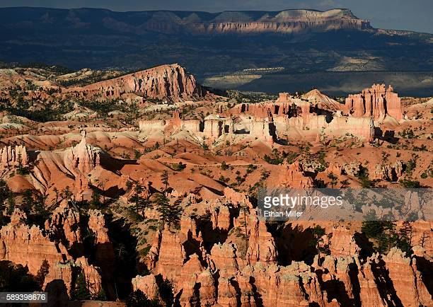 The sloped Sinking Ship formation and the Aquarius Plateau are illuminated by the setting sun above hoodoos viewed from Sunset Point overlooking...