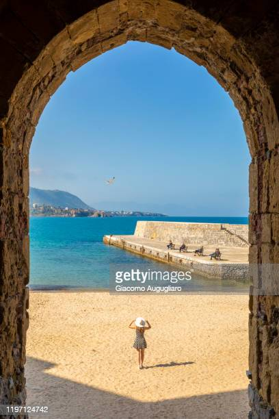 the small beach of cefalù viewed through an arch, palermo province, sicily, italy - sud foto e immagini stock