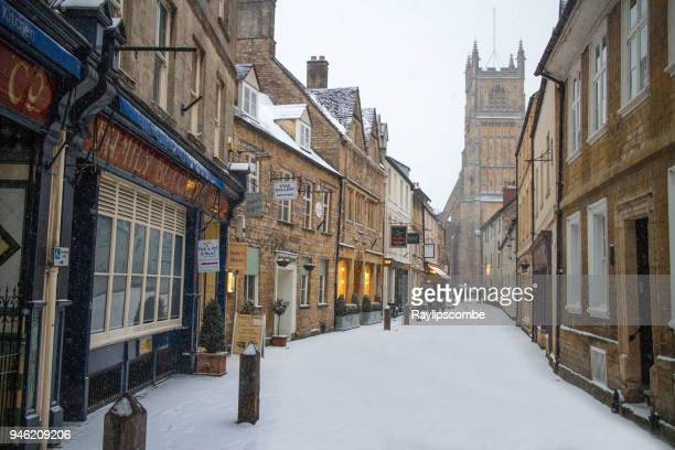 The small, quaint Blackjack Street in Cirencester, The Cotswolds with small shops and the parish church in the background, covered in snow