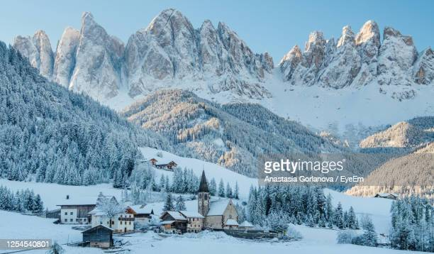 the small village val di funes covered in snow, with dolomites mountains, south tyrol, italy. - valle foto e immagini stock