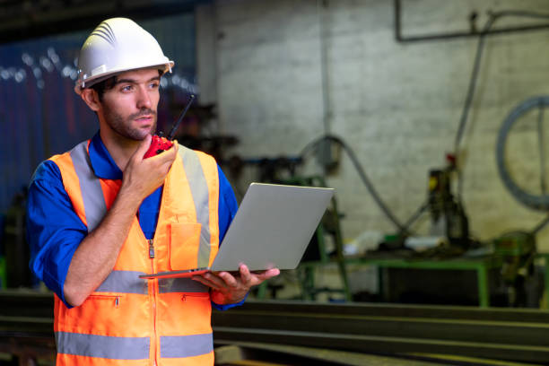 The smart engineer working and wearing protection wear with  walkie talkie  with laptop in factory.